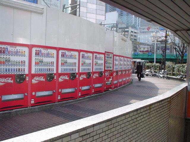 工事の目隠し板に自販機の絵、所々に本物の自販機。紛らわしい……